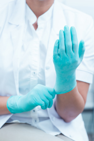 surgical coat: Close up mid section of female dentist wearing surgical glove