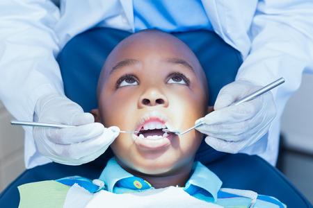 dentista: Primer plano de chico que hace sus dientes examinados por un dentista
