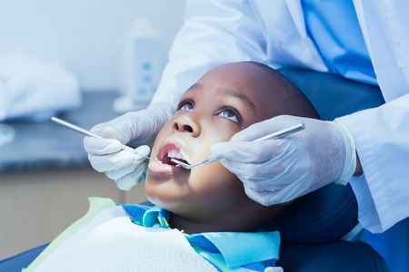 a dentist: Close up of boy having his teeth examined by a dentist