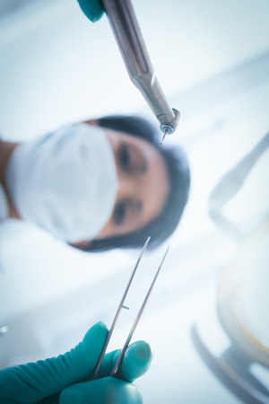 Low angle view of female dentist in surgical mask holding dental tools photo