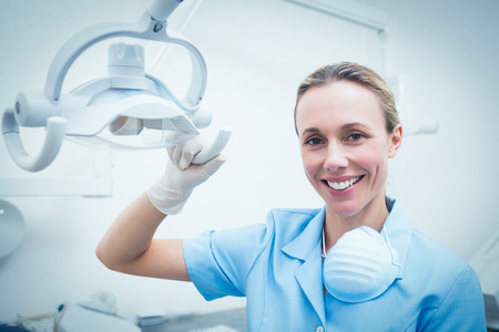 Portrait of smiling young female dentist adjusting light Stock Photo