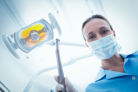 surgical tool: Low angle portrait of female dentist in surgical mask holding dental tool Stock Photo