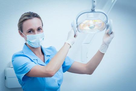 surgical light: Portrait of female dentist in surgical mask adjusting light