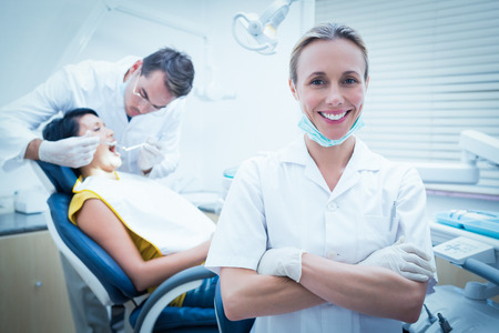 Portrait of smiling female dentist with assistant examining womans teeth in the dentists chair