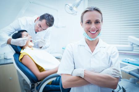 도우미와 치과 의사 의자에서 여자 치아를 검사와 웃는 여성 치과 의사의 초상화 스톡 콘텐츠