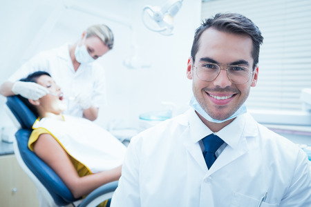 Portrait of smiling male dentist with assistant examining womans teeth in the dentists chair Stock Photo