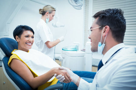 치과 의자에 여자와 악수 남성 치과 의사 스톡 콘텐츠