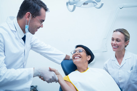 male dentist: Male dentist shaking hands with woman in the dentists chair Stock Photo