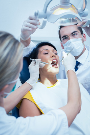 a dentist: Male dentist with assistant examining womans teeth in the dentists chair Stock Photo