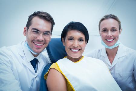 dentista: Retrato de la sonrisa del dentista masculina y ayudante con el paciente femenino en la silla de los dentistas Foto de archivo