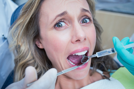 syringes: Close up of woman having her teeth examined by dentist and assistant