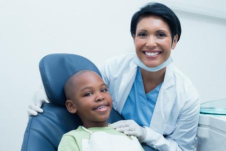 dentist woman: Portrait of female dentist examining boys teeth in the dentists chair
