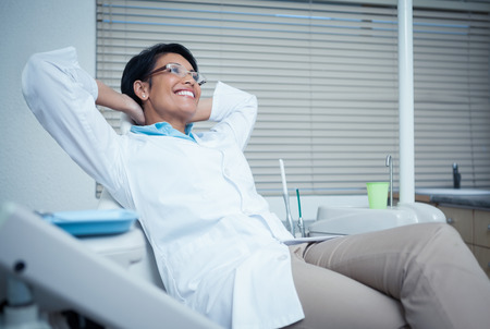 hands behind head: Relaxed smiling female dentist sitting on chair with hands behind head