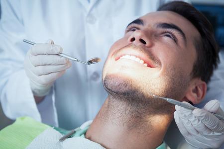 dental examination: Close up of man having his teeth examined by dentist Stock Photo
