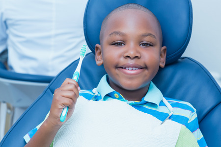 Portrait of young boy holding toothbrush in the dentists chair photo