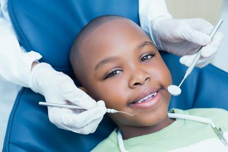 彼の歯は、歯科医によって検討を持つ少年のクローズ アップ