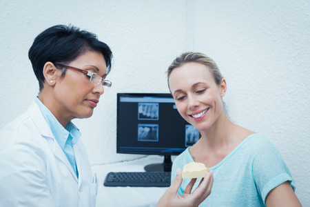 prosthesis: Female dentist showing happy woman prosthesis teeth