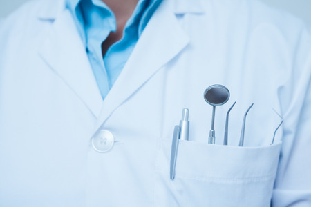 dentist woman: Close up mid section of dental tools in dentists pocket