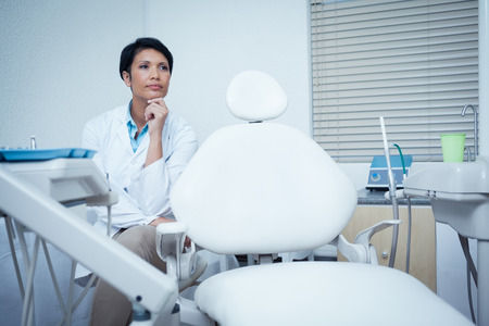 Thoughtful young female dentist looking away Stock Photo