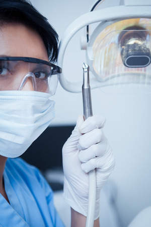 Portrait of female dentist in surgical mask holding dental drill photo