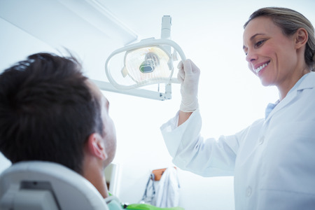 mid adult   female: Female dentist examining mans teeth in the dentists chair