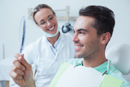 a dentist: Smiling young man looking at mirror in the dentists chair Stock Photo