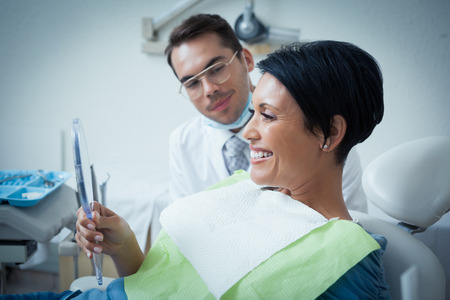 a dentist: Side view of smiling female patient with dentist in the dentists chair Stock Photo