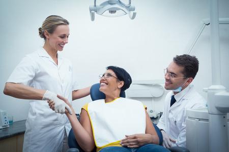 dentista: Dentista de sexo masculino con el ayudante estrechando la mano de la mujer en la silla de los dentistas