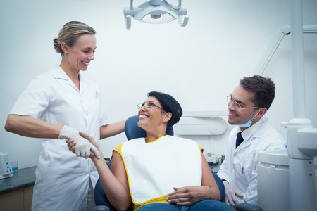 a dentist: Male dentist with assistant shaking hands with woman in the dentists chair Stock Photo