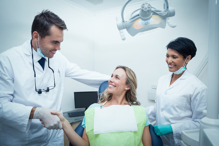 Male dentist with assistant shaking hands with woman in the dentists chair Standard-Bild