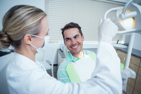 dental clinics: Female dentist examining mans teeth in the dentists chair