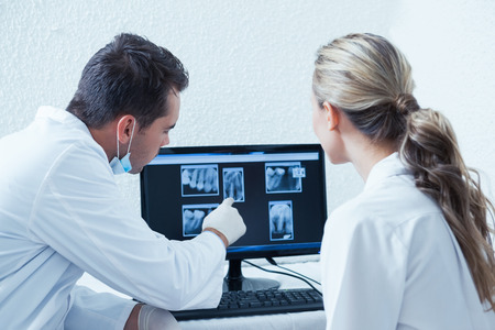 Two concentrated dentists looking at x-ray on computer Stock Photo