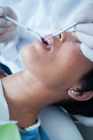 examined: Close up of woman having her teeth examined by dentist Stock Photo