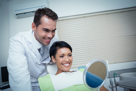 woman mirror: Smiling young woman looking at mirror in the dentists chair