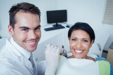dentist and patient: Male dentist examining womans teeth in the dentists chair Stock Photo