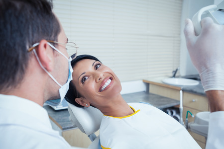 exam: Side view of smiling young woman waiting for a dental exam