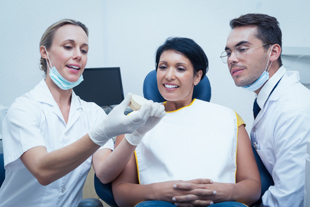 prosthesis: Female dentist with assistant showing woman prosthesis teeth