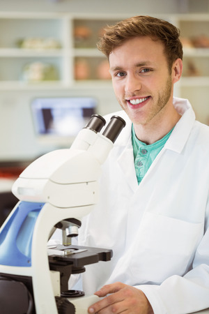 Young scientist working with microscope at the university photo