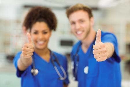 estudiantes medicina: j�venes estudiantes de medicina que muestran los pulgares para arriba en la universidad