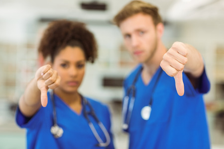 medical students: Young medical students showing thumbs down at the university