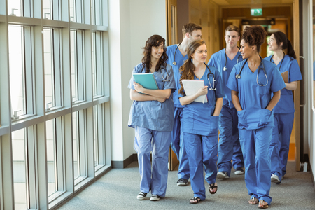 adult students: Medical students walking through corridor at the university