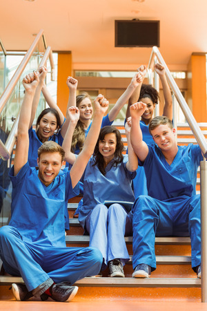 Medical students cheering on the steps at the university Stock Photo