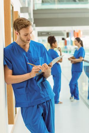 estudiantes medicina: Estudiante de medicina que toma notas en el pasillo de la universidad