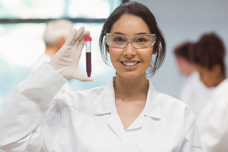 research science: Pretty science student smiling and showing vial at the university