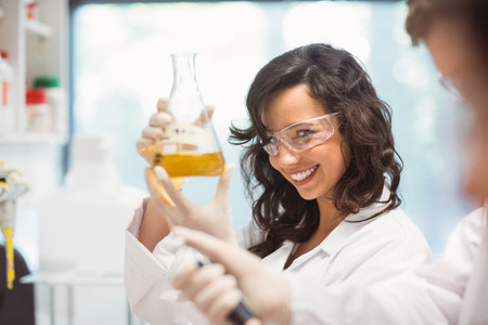 medicine and science: Pretty science student smiling and holding beaker at the university
