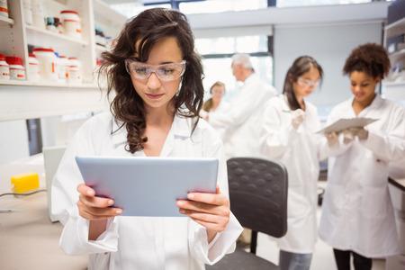 laboratorio: Estudiante de la ciencia que mira la PC de la tableta en el laboratorio de la universidad
