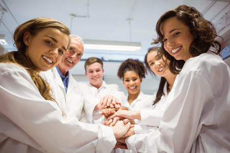 medicine and science: Science students and lecturer putting hands together at the university