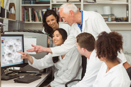 computer science class: Science students looking at microscopic image on computer with lecturer at the university