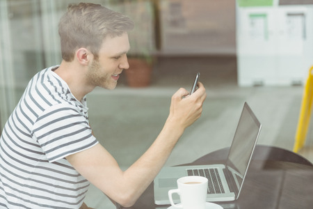 typing man: Smiling student using laptop and smartphone in cafe at the university Stock Photo