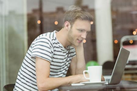 cafe internet: El estudiante sonriente usando la computadora port�til en la cafeter�a de la universidad Foto de archivo